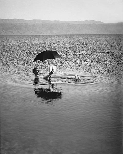 Man Floats in Dead Sea w/ Book & Umbrella Photo Print for Sale