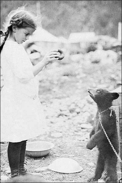 Girl Teasing Bear Cub w/ Doughnut Photo Print for Sale